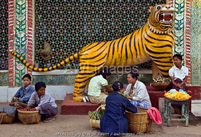 Myanmar. Burma. Popa. Food and flower sellers beside a statue of a tiger at the foot of Mount Popa.