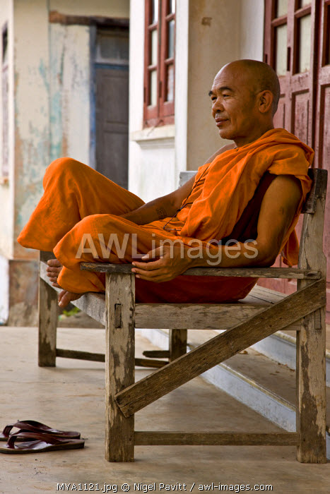 Myanmar. Burma. Popa. A Buddhist monk relaxes on his verandah at the foot of Mount Popa.