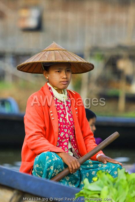 Myanmar. Burma. Lake Inle. A Burmese girl selling vegetable at the floating market of Ywa-ma on Lake Inle.