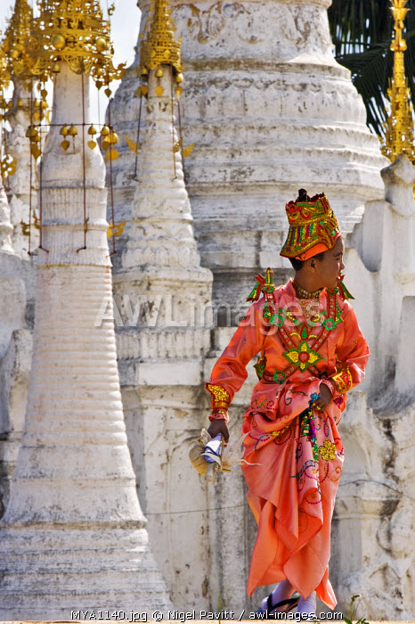 Myanmar. Burma. Lake Inle. A young novitiate passes an ornate Buddhist shrine during a ceremony in which the boy is inducted as a novice Buddhist monk.