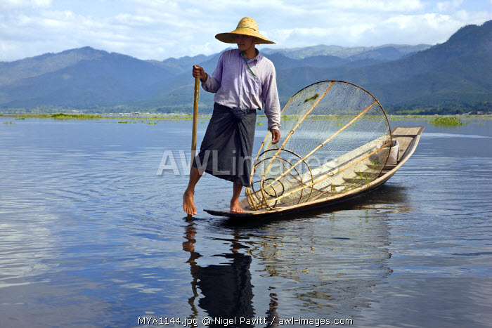 Myanmar. Burma. Lake Inle. An Intha fisherman with a traditional fish trap uses an unusual leg-rowing technique to propel his flat-bottomed boat across the lake while standing.