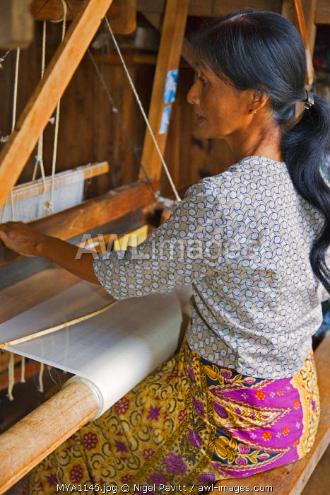 Myanmar, Burma, Lake Inle. A woman weaves lotus fibres to produce very fine cloth, more expensive than silk. Lotus weaving has existed at Lake Inle for 90 years and nowhere else.