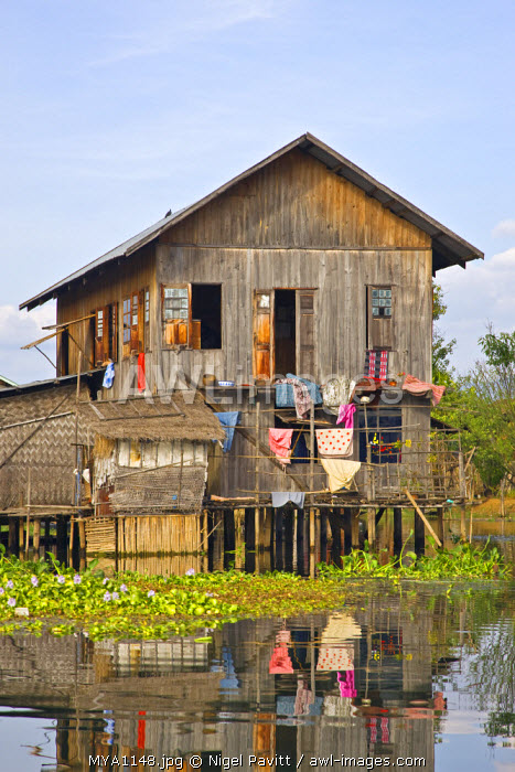 Myanmar, Burma, Lake Inle. A typical Intha wooden house on stilts in Lake Inle, picturesquely sheltered by mountains rising to 1,524 metres.