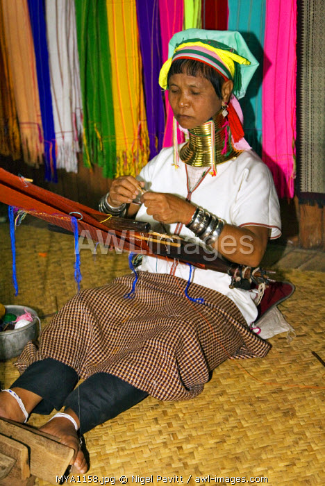 Myanmar, Burma, Lake Inle. A Padaung woman wearing a heavy brass necklace weaves cloth on a simple loom, her back supported by a strap attached to the loom's wooden frame.