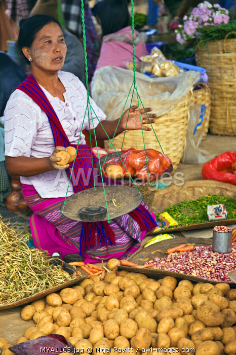 Myanmar, Burma, Lake Inle. A woman weighs potatoes at the popular Phaung Daw Oo market where all kinds of farm produce are sold.