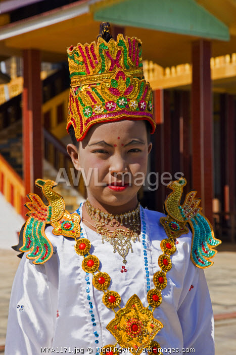 Myanmar, Burma, Lake Inle. A young novitiate pauses beside an ornate Buddhist monastery during a ceremony in which the boy is inducted as a novice Buddhist monk.