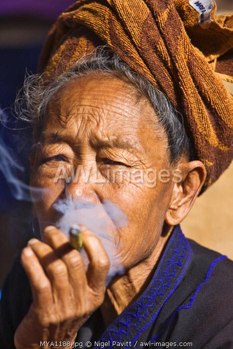 Myanmar, Burma, Lake Inle. An old Pa-O woman smokes a cheroot.