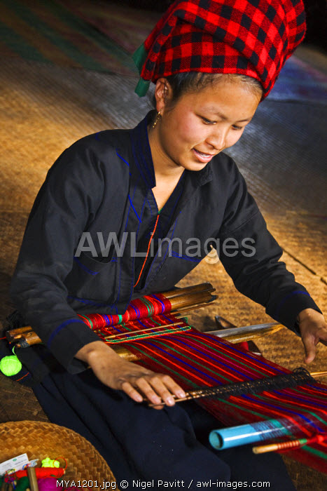 Myanmar, Burma, Lake Inle. A pretty Pa-O woman weaves brightly coloured material at Kya-Toon village.