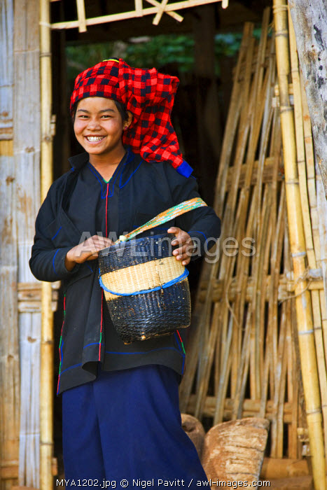 Myanmar, Burma, Lake Inle. A happy Pa-O woman leaves her house at Kya-Toon village carrying a woven bamboo basket.