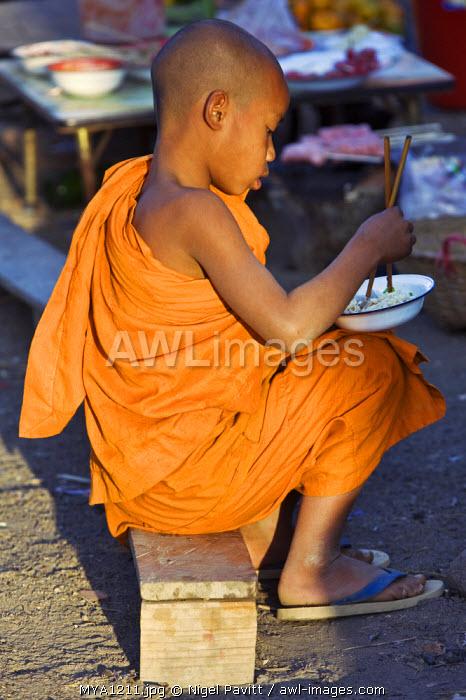 Myanmar. Burma. Wanpauk village. A novice monk eating noodles with chopsticks at Wanpauk village market.