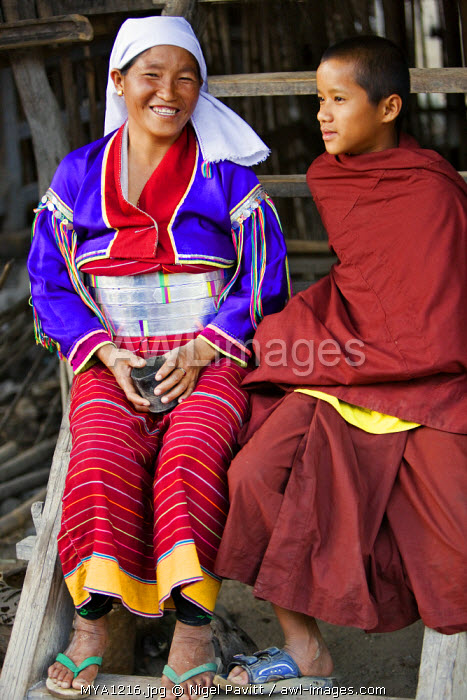 Myanmar. Burma. Wanpauk village. A proud Palaung woman sits beside her son – a novice monk.  She displays her wealth by wearing broad silver belts around her waist.