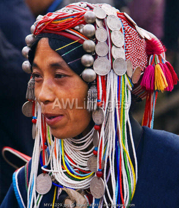 Myanmar, Burma, Kengtung. An Akha woman wearing a traditional headdress of silver and beads.