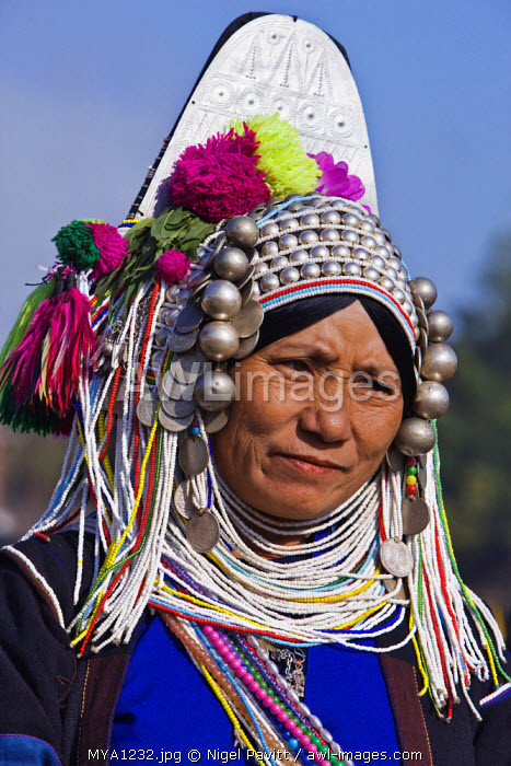 Myanmar, Burma, Kengtung. A Mong la Akha woman wearing a traditional headdress of silver and beads.