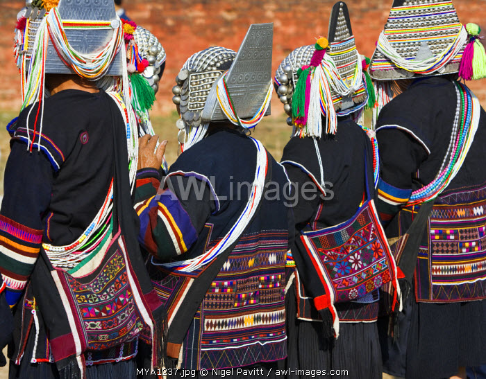 Myanmar, Burma, Kengtung. Akha women wearing embroidered jackets and traditional headdresses of silver and beads.