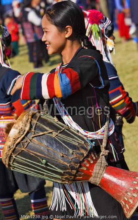 Myanmar, Burma, Kengtung. An Akha woman wearing traditional costume beats a drum during an Akha festival.