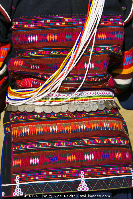 Myanmar, Burma, Kengtung. The beautiful embroidery on an Akha woman's jacket and a beaded belt from which are hung old silver Burmese coins.