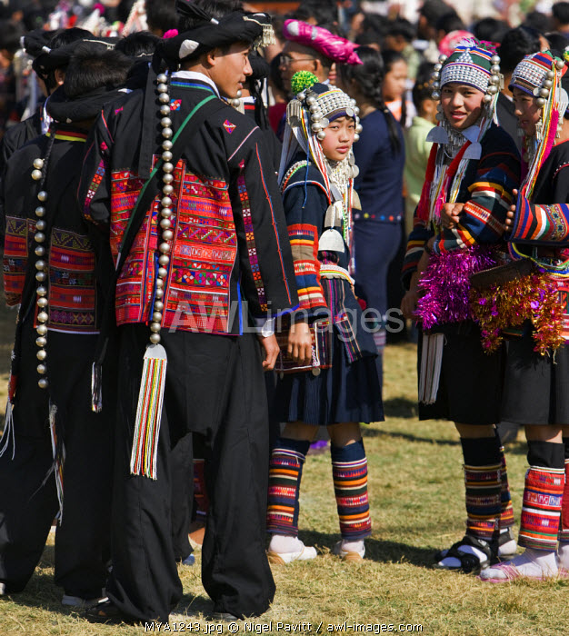 Myanmar, Burma, Kengtung. A gathering of Akha men and women wearing traditional costumes at an Akha festival.