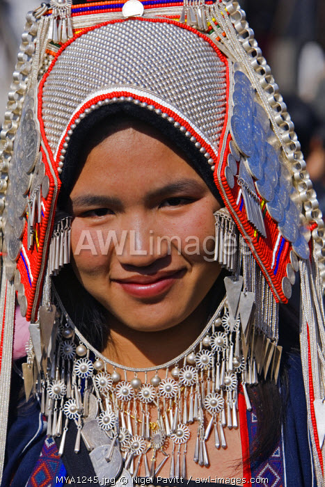 Myanmar, Burma, Kengtung. An Akha woman wearing traditional costume with a headdress of silver and glass beads.