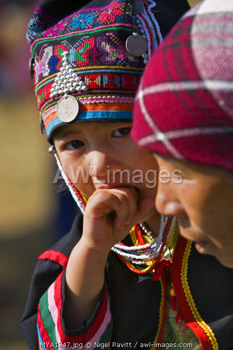 Myanmar, Burma, Kengtung. A young Akha boy wearing a colourful embroidered hat while carried by his mother.