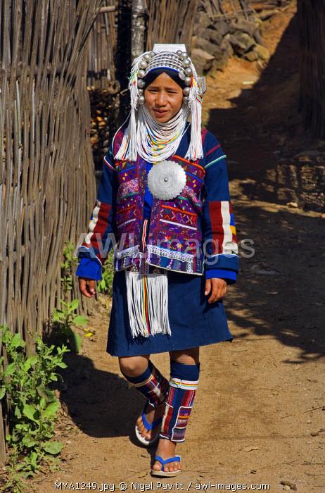 Myanmar, Burma, Namu-op. An Akha woman wearing traditional costume with a headdress of silver and glass beads.