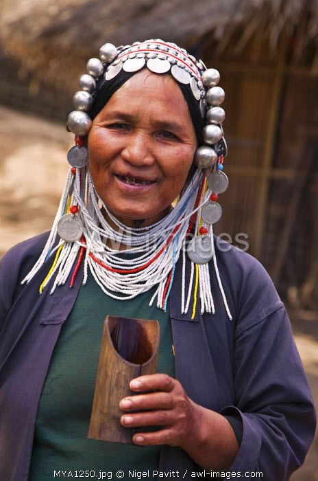 Myanmar, Burma, Namu-op. An Akha woman wearing traditional costume with a headdress of silver and glass beads holds a bamboo mug in her hand.
