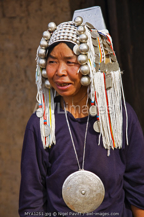 Myanmar, Burma, Namu-op. An Akha woman wearing traditional costume with a headdress of silver and glass beads, and a fine Phè gho pendant.