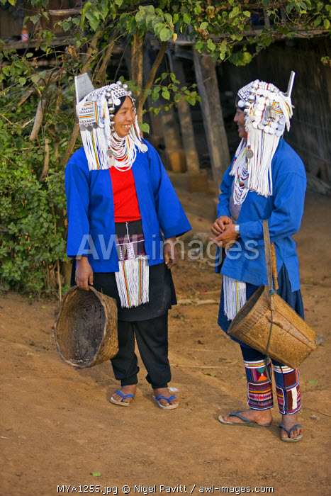 Myanmar, Burma, Namu-op. Two Akha women in all their finery pause to chat in Namu-op village.