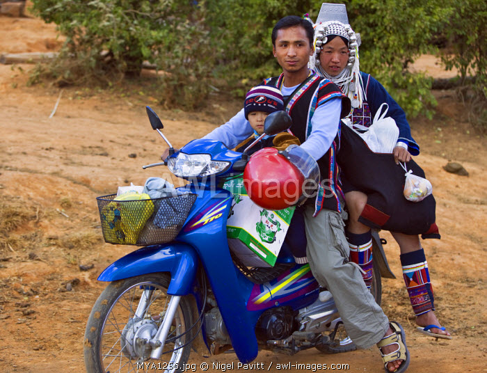 Myanmar, Burma, Namu-op. An Akha family with baggage just manages to ride on one motorcycle near Namu-op village.