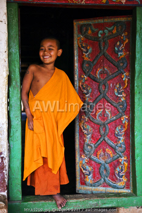 Myanmar, Burma, Ban-lo. A young novice monk at the carved doors of Ban-lo monastery outside Kengtung.