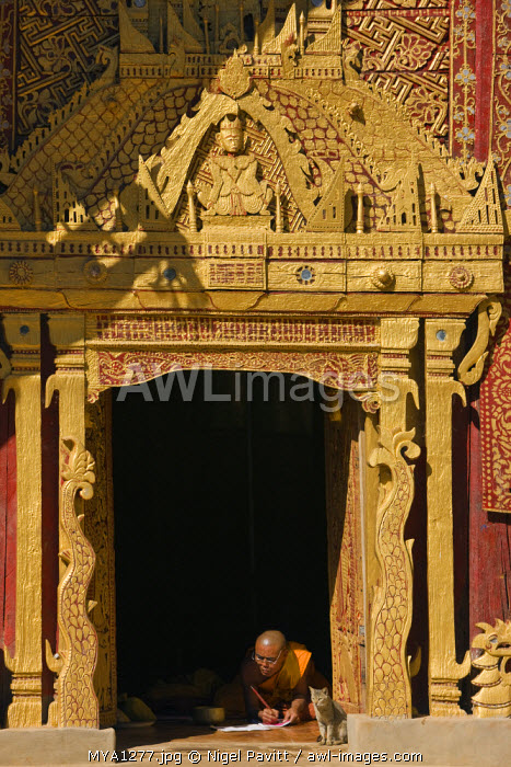 Myanmar, Burma, Wun nyat. The abbot scribes at the doorway to beautiful Wun nyat monastery. Built in the 15th century, it was renovated in the 17th and 18th centuries.
