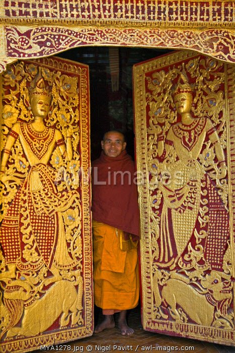 Myanmar, Burma, Wun nyat. The abbot closes the ornate door to beautiful Wun nyat monastery. Built in the 15th century, it was renovated in the 17th and 18th centuries.