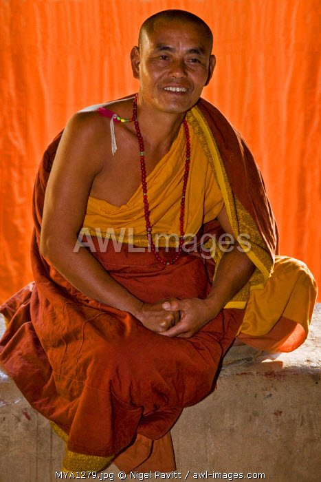 Myanmar, Burma, Wun nyat. The friendly abbot of the beautiful Wun nyat monastery meditates, shielded from the sun by a saffron robe.