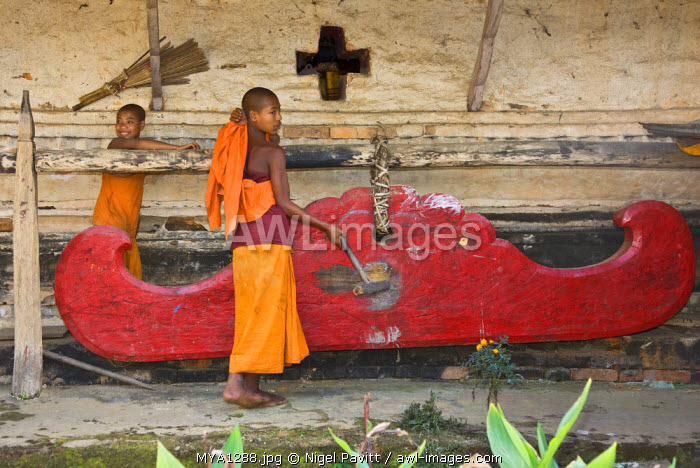 Myanmar, Burma, Wan-seeing.  A novice monk sounds the huge wooden gong outside the beautiful 15th or 16th century Wan-seeing monastery.
