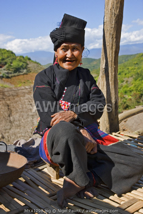 awl-images.com - Myanmar / Myanmar, Burma, Wan doi. An Ann woman in traditional dress sits on the raised platform of her house at Wan doi village.