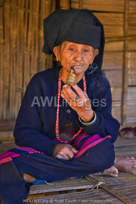 Myanmar, Burma, Wan doi. An old woman of the small Ann tribe in traditional attire sitting on the raised platform of her house as she smokes a pipe.