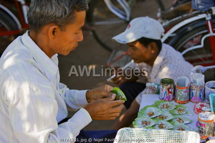 Myanmar, Burma, Yangon. The owner of a small street stall prepares beetle nut wrapped in lime-coated betel leaves.  When chewed, it acts as a mild stimulant staining the mouth deep red.