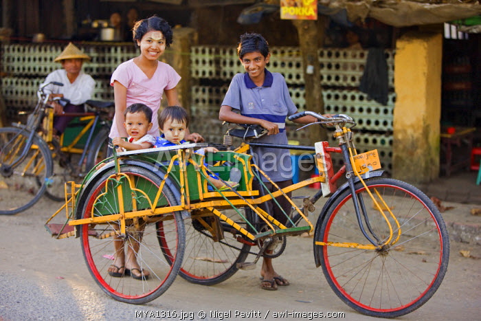 Myanmar, Burma, Sittwe.  A Burmese family takes to the streets of Sittwe in a trishaw, a popular means of transport in which passengers sit back to back in a sidecar.