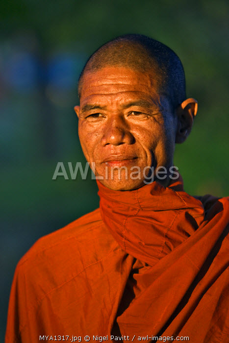 Myanmar, Burma, Rakhine State. A Buddhist monk enjoys the late afternoon at Sittwe, a bustling port town where the waters of the wide Kaladan River enter the sea at the Bay of Bengal.
