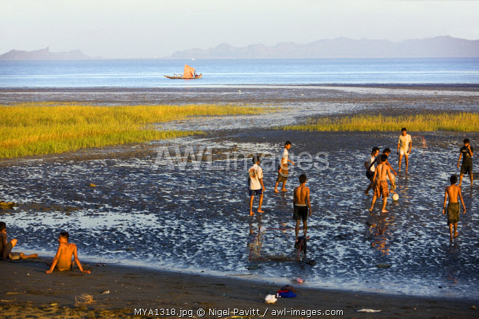 Myanmar, Burma, Rakhine State. In the late afternoon, youths play football on one of Sittwe's tidal beaches.