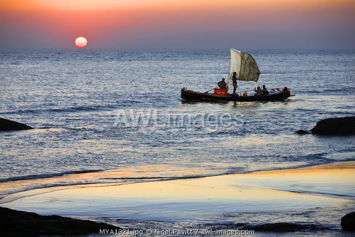 Myanmar, Burma, Rakhine State. The crew of a fishing boat hurries home to Sittwe as the sun sets over the Bay of Bengal.