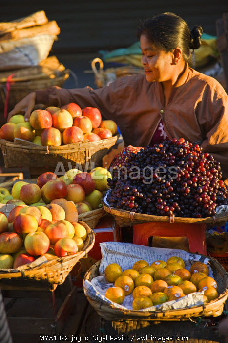 awl-images.com - Myanmar / A woman sells a delicious selection of fresh fruit at Sittwe's bustling market.