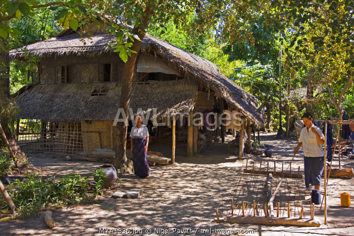 Myanmar, Burma, Kaladan River. A Burmese woman of the Rakhine ethnic group preparing skeins of wool for weaving. Most Rakhine women are expert weavers.