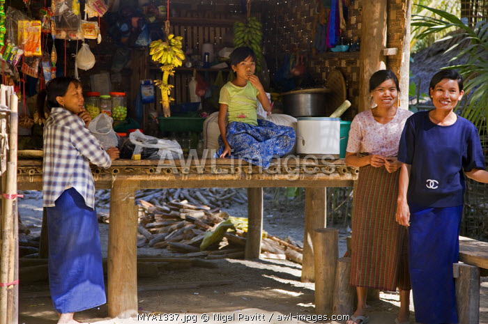 Myanmar, Burma, Kaladan River. Burmese women and a girl of the Rakhine ethnic group at the village shop of Wa Bo situated on the banks of the Kaladan River.