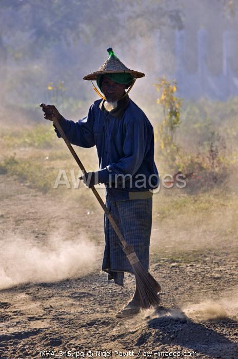 Myanmar, Burma, Mrauk U. An old man sweeps the road at Mrauk U.