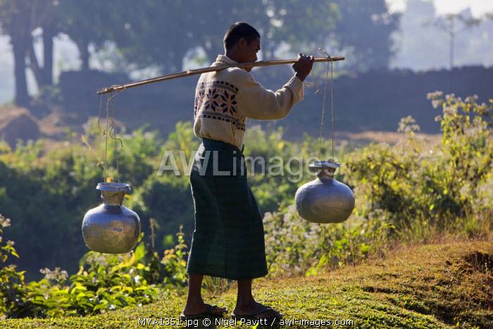 Myanmar, Burma, Mrauk U. A Rakhine man carries water in aluminium pots near Mrauk U.