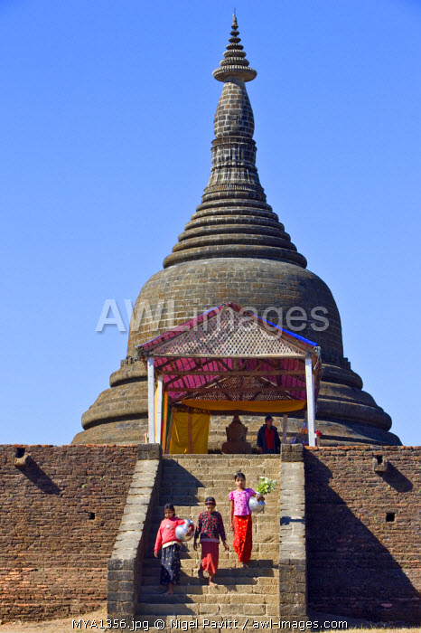Myanmar, Burma, Mrauk U. Girls walking down the steps of the massive bell-shaped Koe Thung temple, the temple of 90,000 Buddhas, built by King Min Taik Kha in 1553.