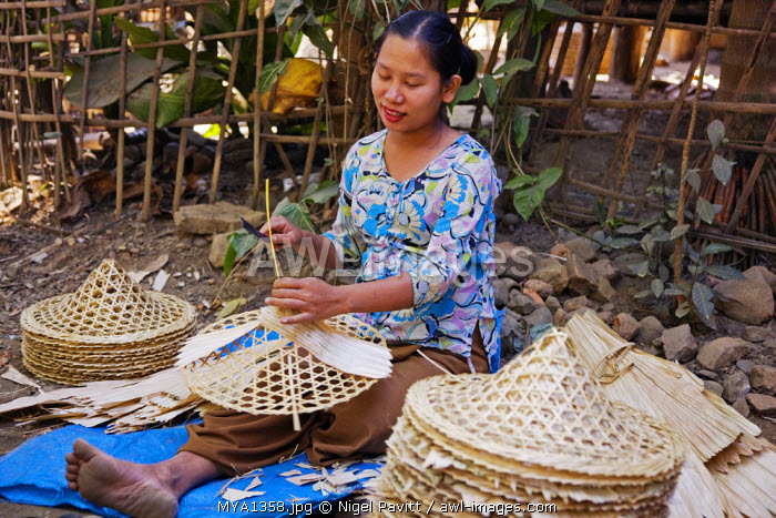 Myanmar, Burma, Mrauk U. A woman skilfully applies bamboo sheaths to the bamboo frame of a conical, wide-brimmed hat which are so popular in the Far East.