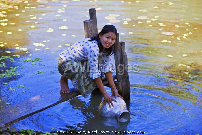 Myanmar, Burma, Mrauk U. A young Rakhine woman draws water in an aluminium pot from a rainwater pond near her village.