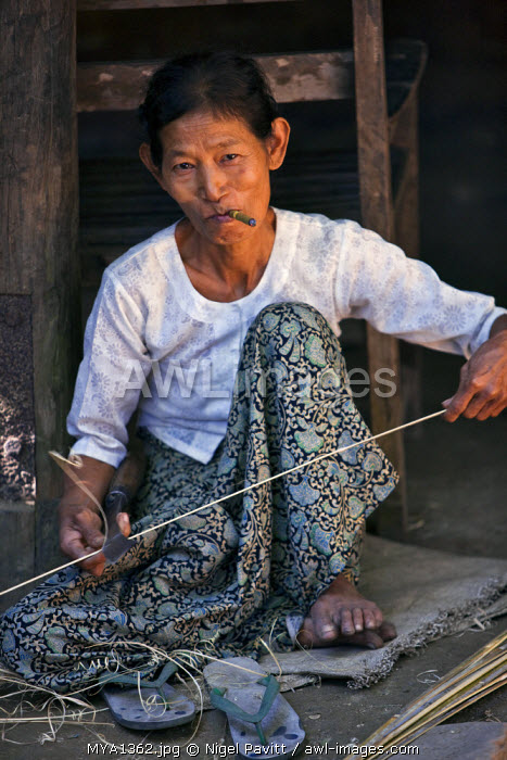 Myanmar, Burma, Mrauk U. A Rakhine woman smokes a cheroot as she splits bamboo in readiness to make the frame of a wide-brimmed, bamboo hat.
