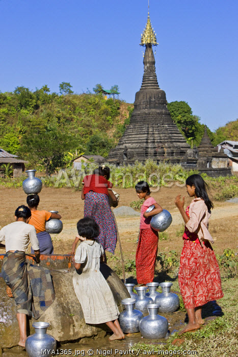 awl-images.com - Myanmar / Myanmar, Burma, Mrauk U. Against a backdrop of ancient temples, Rakhine women draw water from a well at Mrauk U. Their aluminium water containers are imported from India.